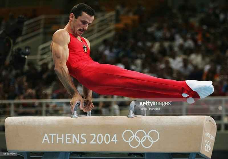 ATHENS - AUGUST 16: Marius Daniel Urzica of Romania competes on the pommel horse in men's artistic gymnastics team final competition on August 16, 2004 during the Athens 2004 Summer Olympic Games at the Olympic Sports Complex Indoor Hall in Athens, Greece. (Photo by Clive Brunskill/Getty Images) *** Local Caption *** Marius Daniel Urzica