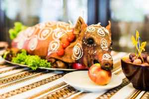 62309616 - decorated and roast suckling pig with an apple in his mouth on a white plate on banquet